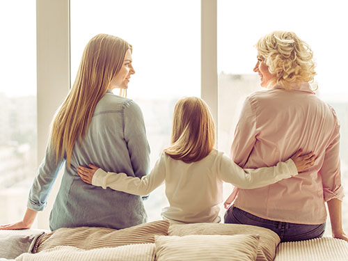 Daughter linking mother and grandmother together with her hands on their backs during emotion focused caregiver workshop