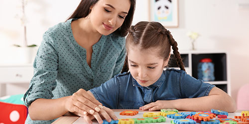 Mother and daughter in parent-child therapy session using blocks