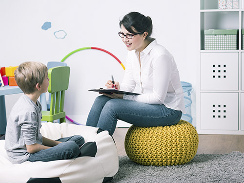 Child therapist writing on clipboard while talking to young child