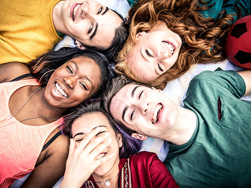 Group of happy teens with colorful t-shirts lying down in a circle smiling and laughing