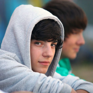 Lonely teenage boy in grey hoodie looking to his right