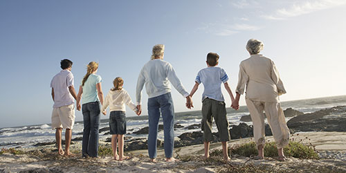 Family united and linking hands on a rocky beach and staring out to sea