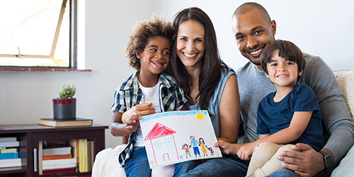 Young family with 2 parents and 2 children sitting in family therapist's office smiling and holding up children's picture