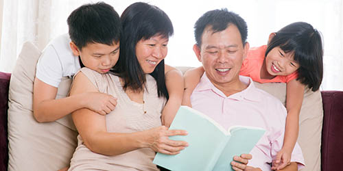 Family reading a book together on their therapist couch
