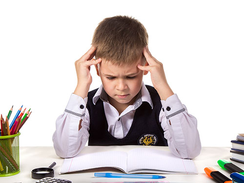 Frustrated child holding hands against his head while staring at school work