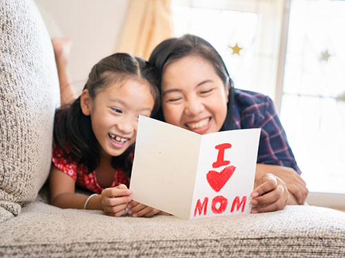 Mother and daughter reading I love you mom card on couch during emotion focused caregiver workshop