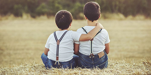 Two brothers in overalls sitting in farmers field with supportive hand on brothers shoulder