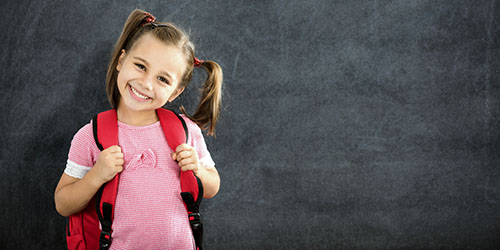 Young girl with red backpack looking forward and smiling with chalkboard in the background