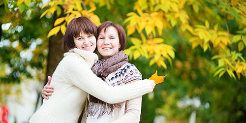 Daughter and mother hugging each other outside in the chilly weather in front of a yellow tree