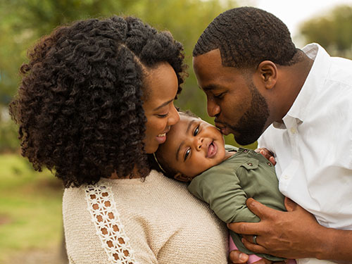 Parents after emotion focused caregiver workshop kissing baby